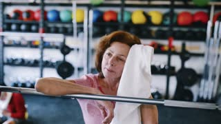 Senior woman in gym resting, wiping sweat with towel