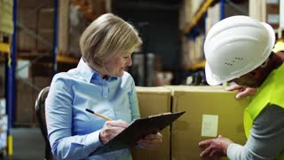 Senior woman manager and a man worker working together in a warehouse.