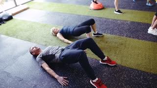 Senior woman with coach in gym doing bridge exercise.