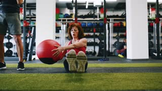 Senior woman working out her abs with medicine ball.