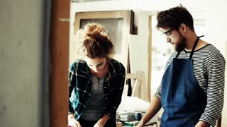 Small business of a young couple. A man and woman worker in the carpenter workroom.