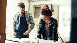 Small business of a young couple. Man and woman worker in the carpenter workroom