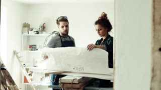 Small business of a young couple. Man and woman worker in the carpenter workroom.