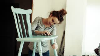 Small business of a young woman. Beautiful young woman worker in carpenter workroom. Old furniture restoration. Slow motion.