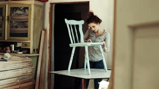 Small business of a young woman. Beautiful young woman worker in carpenter workroom. Old furniture restoration.