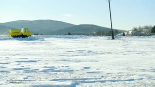 Snowplough clearing road in winter nature.