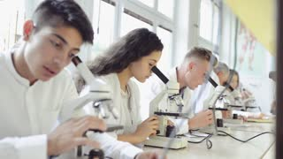 Teacher teaching biology to high school students in laboratory.