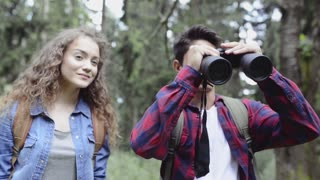 Teenage couple hiking in forest. Summer vacation.