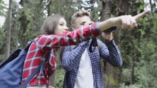 Teenage couple with binoculars hiking in forest. Summer vacation adventure.