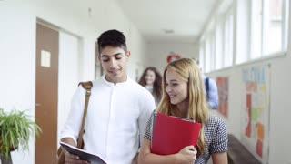 Teenage students walking in high school hall, talking.