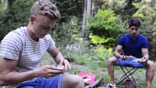 Teenagers camping, eating meat cooked on barbecue grill.