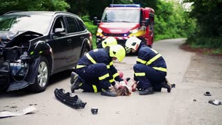 Three firefighters rescuing a young injured woman lying unconscious on the road after an accident. Slow motion.