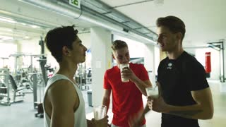 Three young fit men in gym talking together, drinking shakes.