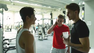 Three young fit men in gym talking together, laughing, shaking hands.