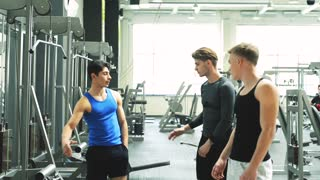 Three young fit men, one of them leaving and saying goodbye after working out in gym.