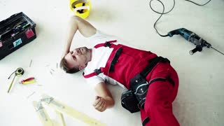 Top view of an injured man in pain lying on the floor after an accident at work. Slow motion.