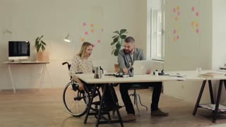 Two business people in the office working together. A man and woman in a wheelchair celebrating success. Slow motion.