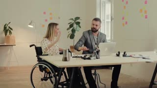 Two business people in the office working together. A man and woman in a wheelchair celebrating success. Slow motion