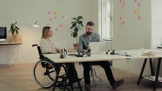 Two business people in the office working together. A man and woman in a wheelchair celebrating success