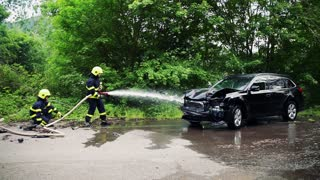 Two firefighters extinguishing a burning car after an accident on the road in the countryside. Slow motion.