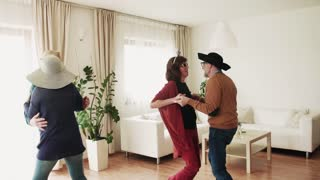 Two happy senior couples dancing at the party at home, having fun. Slow motion.
