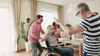 Two happy senior couples with wheelchair dancing at the party at home, having fun. Slow motion.