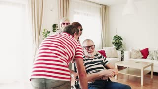 Two happy senior couples with wheelchair having fun at the party at home. Slow motion.