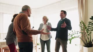 Two senior couples greeting one another at a party at home. Old men and women holding a bottle of wine and a plant, celebrating.