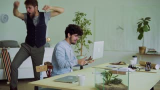 Two young men working together in an office, celebrating success. Start-up business. Slow motion