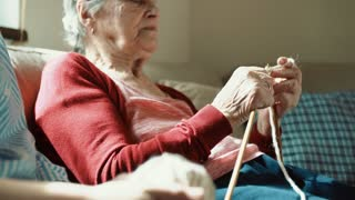 Unrecogniazable elderly grandmother and adult granddaughter at home, knitting. Close up.