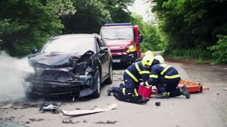 Unrecognizable firefighters rescuing a young injured woman lying on the road after an accident. Slow motion.