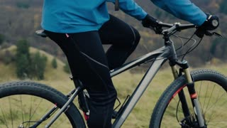 Unrecognizable man riding his bicycle outside in autumn nature. Slow motion