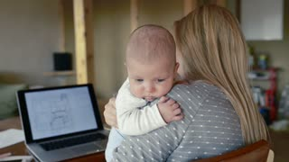 Unrecognizable young blond mother at home with her little baby son in the arms, sitting at the table, working on laptop