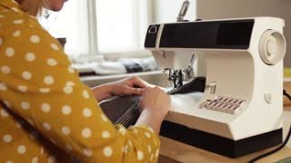 Unrecognizable young creative woman using sewing machine, startup business.