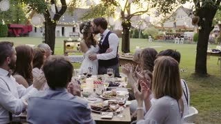Wedding reception outside in the backyard. Bride and groom kissing each other. Family around the table, clapping. Slow motion.