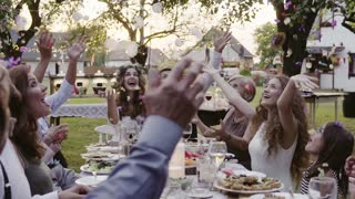 Wedding reception outside in the backyard. Bride and groom with a family around the table, having fun. Slow motion.