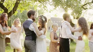 Wedding reception outside in the backyard. Bride and groom with a family dancing. Slow motion.
