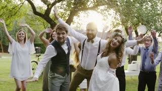 Wedding reception outside in the backyard. Family celebration. Bride, groom and their guests posing for the photo, having fun. Slow motion.