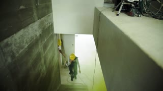 Woman and man workers running up the stairs at the construction site, suffocating. Carbon monoxide poisonous gas cloud. Slow motion.