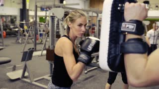 Woman in gym boxing with her personal trainer.
