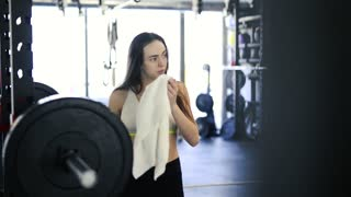 Woman in gym wiping sweat off her face, drinking water.