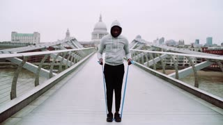 Young active black sportsman exercising with elastic rubber bands on the bridge in London, St. Paul's Cathedral in the background. Slow motion.