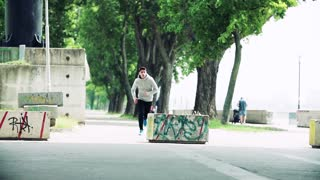 Young athlete man running on the street in the city, jumping over concrete flower pot. Slow motion.