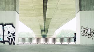 Young athlete woman running under the concrete bridge in the city. Slow motion.