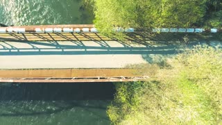 Young athletes running on rusty bridge above the river in sunny autumn nature. Trail runner training for cross country running. Aerial view.