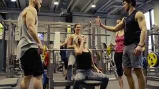 Young beautiful fit woman in gym with her friends doing high five after finishing bench presses.