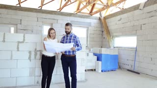 Young couple at the construction site. A man and woman looking at plans of the new house, discussing issues at the construction site.