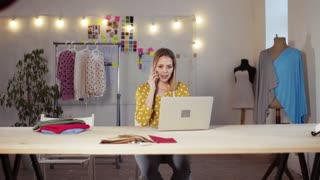 Young creative woman with laptop and smartphone working in a studio, startup business.