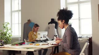 Young creative women with sewing machine working in a studio, startup business.