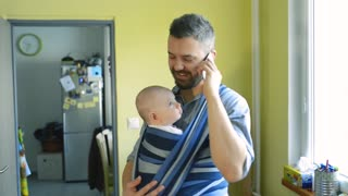 Young father at home with his newborn baby son in sling holding smart phone, making phone call, talking. Little girl running around.